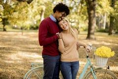 Ajouter multiraciaux à la bicyclette en parc d'automne photos stock
