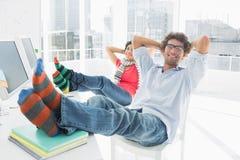 Ajouter occasionnels décontractés aux jambes sur le bureau dans le bureau Images stock
