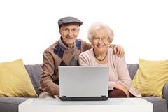 Ajouter pluss âgé à un ordinateur portable se reposant sur un sofa Photo stock