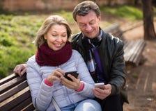 Ajouter pluss âgé aux téléphones portables dans la journée de printemps ensoleillée Image stock