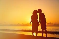 Ajouter romantiques au petit enfant au coucher du soleil Images stock