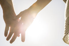 Ajouter romantiques aux mains étreintes éclairées à contre-jour par un s égalisant lumineux Photographie stock