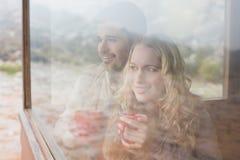Ajouter satisfaits réfléchis aux tasses regardant par la fenêtre Image stock