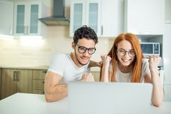Ajouter stupéfaits à la bouche ouverte sur la ligne avec l'ordinateur portable dans le salon dans la maison Images libres de droits