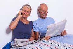 Ajouter supérieurs à la Tablette et au journal dans le lit Photos stock