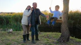 Ajouter supérieurs affectueux au petit-fils reposant au lac que jonc envahi en automne aux vacances banque de vidéos