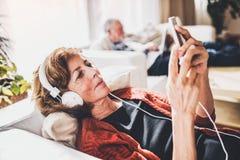 Ajouter supérieurs au smartphone détendant à la maison Photographie stock