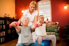 Ajouter supérieurs aux haltères dans la réadaptation avec un physiothérapeute Photos stock