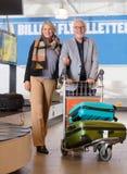 Ajouter supérieurs d'affaires au bagage dans le chariot à l'aéroport Photos libres de droits