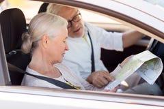 Ajouter supérieurs heureux à la carte conduisant dans la voiture Photographie stock libre de droits