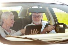 Ajouter supérieurs heureux au PC de comprimé conduisant dans la voiture Image stock