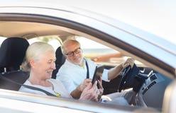 Ajouter supérieurs heureux au PC de comprimé conduisant dans la voiture Images stock