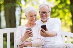 Ajouter supérieurs heureux aux smartphones au parc Photos stock