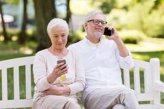 Ajouter supérieurs heureux aux smartphones au parc Photographie stock libre de droits