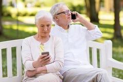 Ajouter supérieurs heureux aux smartphones au parc Photos libres de droits