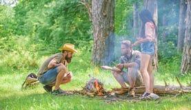 Ajoutez du bois au feu Les amis tra?nent pr?s du pique-nique de feu La for?t de camp de jeunes de soci?t? pr?parent le feu pour l image stock