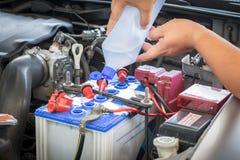 Ajoutez l'eau distillée dans la batterie photos stock