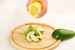 Ajoutez le jus de citron à l'avocat image stock