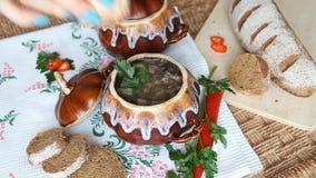 Ajoutez le sel à la soupe dans un pot sur une table russe de vacances banque de vidéos
