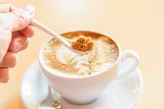 Ajoutez le sucre au café chaud photo stock