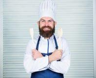 Ajoutez quelques épices Homme avec la barbe dans le chapeau de cuisinier et prise de tablier faisant cuire des outils Cuisson en  image libre de droits