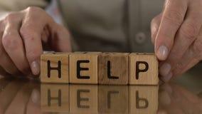Ajuda, ancião que fazem a palavra de cubos de madeira, apoio e auxílio para pessoas idosas filme