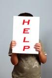 Ajuda - criança isolada no fundo cinzento Fotos de Stock