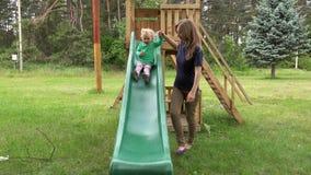 Ajuda cuidadosa da mãe sua filha da criança a deslizar para baixo no campo de jogos video estoque