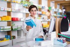 Ajuda de oferecimento do farmacêutico fêmea na escolha no contador no pharma fotos de stock