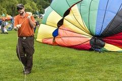 A ajuda do membro de equipagem infla o balão de ar quente Fotos de Stock