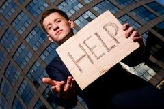 Ajuda do sinal da terra arrendada do homem de negócios ao ar livre Fotografia de Stock Royalty Free