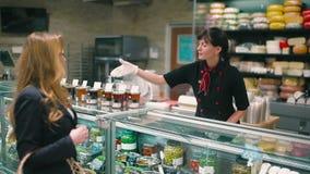 A ajuda do vendedor o louro bonito para escolher o molho no supermercado vídeos de arquivo
