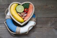Ajuda para o conceito do alimento da dieta da saúde do sumário do coração com boia salva-vidas Fotografia de Stock Royalty Free