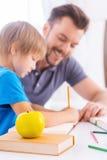 Ajudando ao filho com schoolwork fotografia de stock