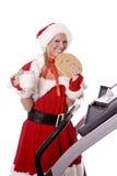 Ajudante de Santa com bolinho e leite grandes na escada rolante Foto de Stock