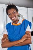 Ajudante fêmea que está com os braços cruzados dentro Foto de Stock