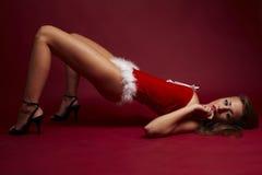 Ajudante 'sexy' de Santa no fundo vermelho Fotografia de Stock Royalty Free