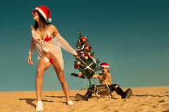 Ajudante 'sexy' de Santa que puxa Santa na praia Foto de Stock