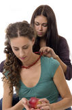 Ajudas da amiga para desgastar grânulos do vermelho da menina Imagem de Stock Royalty Free