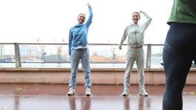 Ajudas do instrutor da aptidão aos gêmeos bonitos das meninas para fazer o esticão do exercício Exercício com instrutor pessoal f video estoque
