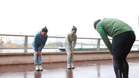 Ajudas do instrutor da aptidão aos gêmeos bonitos das meninas para fazer o esticão do exercício Exercício com instrutor pessoal f filme