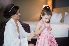 Ajudas do Mum para vestir uma filha pequena Fotografia de Stock