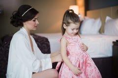 Ajudas do Mum para vestir uma filha pequena Fotografia de Stock Royalty Free