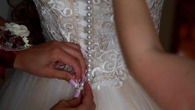Ajudas para atar acima o vestido da noiva video estoque