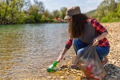 Ajudas volunt?rias da mulher para limpar a costa do rio do lixo Dia da Terra e conceito ambiental da melhoria eco foto de stock