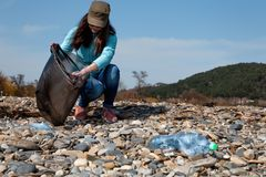 Ajudas voluntárias da mulher para limpar a praia do lixo plástico Dia da Terra e conceito ambiental da melhoria Costa de pedra  imagens de stock