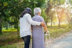 Ajude e importe-se o caminhante superior ou idoso asi?tico do uso da mulher da senhora idosa com sa?de forte ao andar no parque imagens de stock royalty free