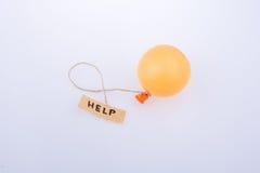 Ajude a exprimir o papel escrito unido a um balão foto de stock