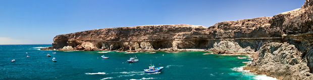 Ajui bay cliffs, Fuerteventura. A bay near Ajui village with fishing boats anchored, Fuerteventura Stock Photography