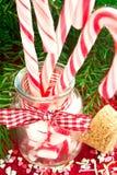 Ajunte bastões de doces listrados no frasco de vidro no fundo do Natal Foto de Stock Royalty Free
